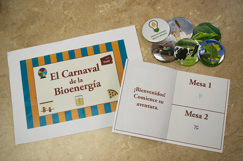 A flyer for the carnival with a striped, circus-like orange and blue background, red lettering that reads El Carnival de la Bioenergia, a bioenergy passport with station 1 stamped, and 6 buttons.