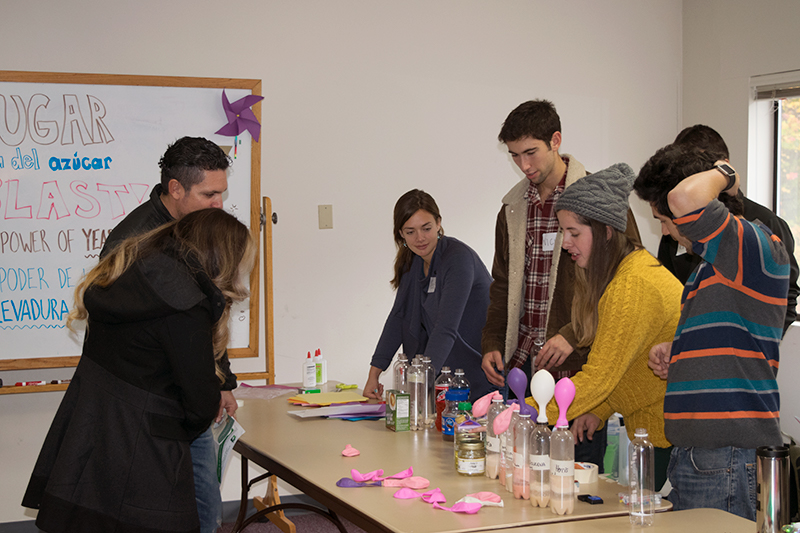 4 NESSP volunteers (2 girls and 2 boys) stand behind a table that has water bottles with different liquids and a balloon attached to the top of each bottle. A couple watches the demonstration.