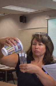 A teacher pouring liquid into test tubes.