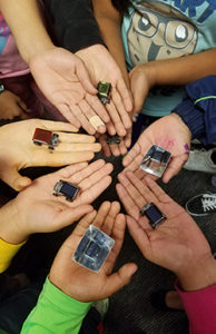 Young hands holding solar cars.
