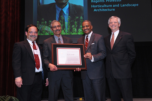 Joe Poovaiah holding the award with Dean Bernardo, President Floyd, and Provost Bailey.