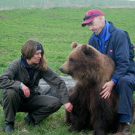 Dr. Charles Robbins and Dr. Lynn Nelson sitting with grizzly bear in yard.