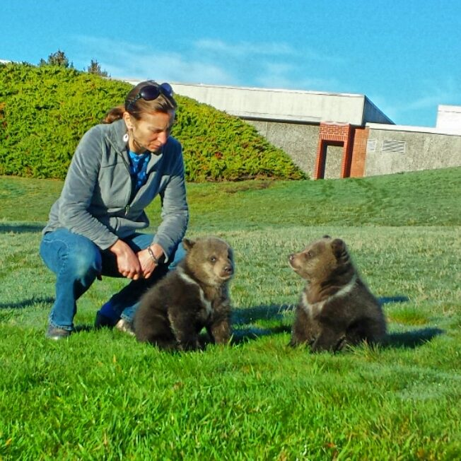 Nina Woodford in a grassy field with two bear cubs.