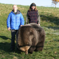 Lynn Nelson and student Jen Fortin standing with bear in yard.