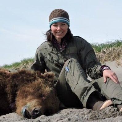 Joy Erlenbach sitting next to a drugged bear.