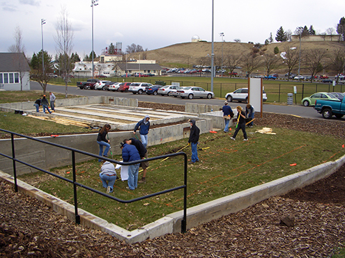 Students working in a grassy area on campus
