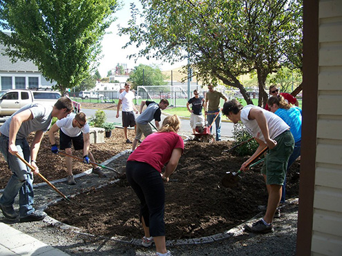 Students shoveling brown earth in a landscaping arrangement