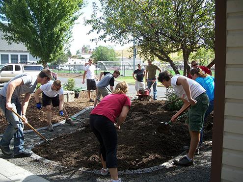 Students shoveling brown earth in a landscaping arrangement