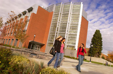 Three students walking in front of building.