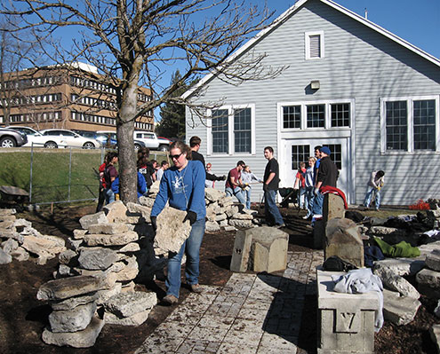 Students carying rocks in a garden area