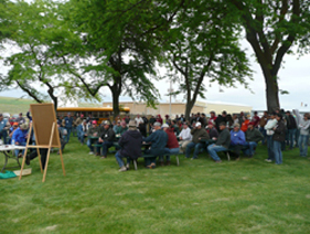 The image shows a crowd listening to a presentation at Lind Field Day.