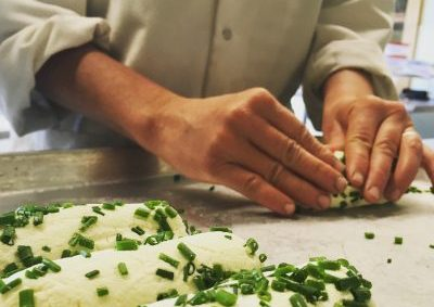 hands rolling goat cheese in chives