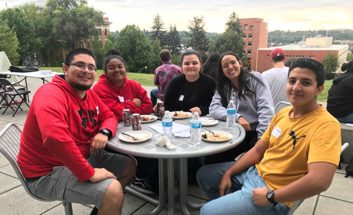 Students eating together outside at the LSAMP program's welcome back BBQ event.