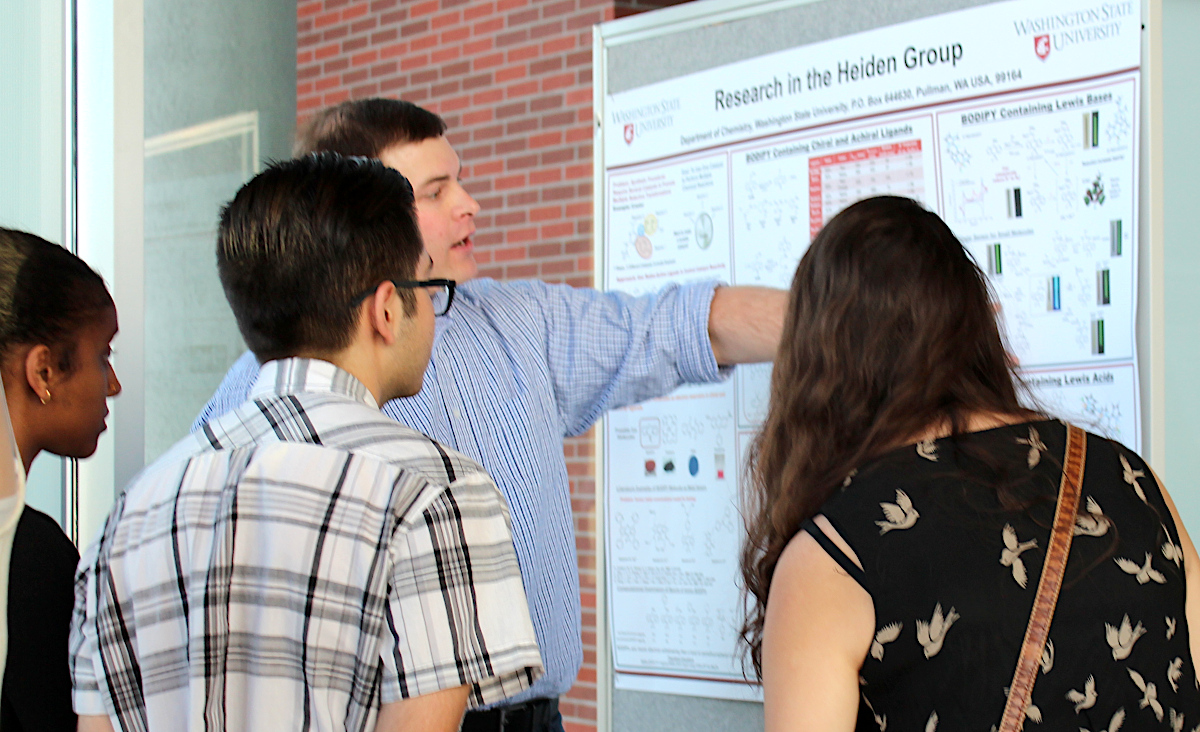 LSAMP students listening to a LSAMP faculty research mentor share his work using a poster as a visual aid.