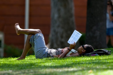 Student reading on the grass.
