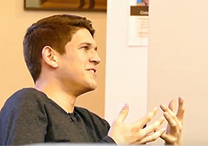 A young man gestures as he speaks.