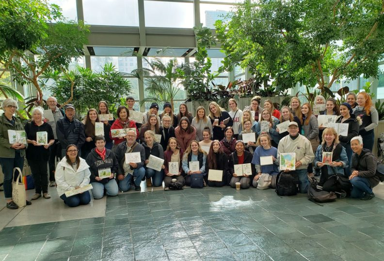 Group photo of students showing their sketches during the interior design study tour in Seattle fall 2019.
