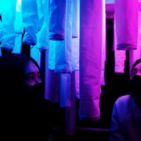 Two masked individuals gaze at their surroundings bathed in blue and pink light.