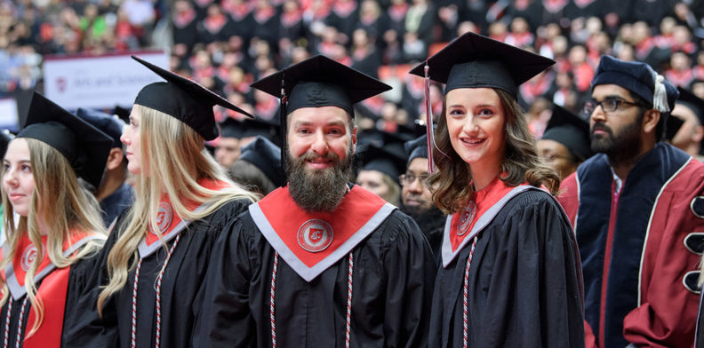 Dan Richer and Kelley Sindelar wearing graduation caps and gowns at a WSU Commencement.