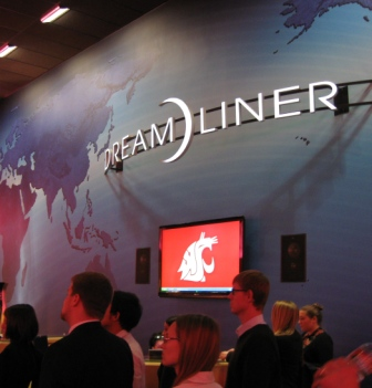 People walking past a wall displaying the Dreamliner logo and the WSU cougar logo.