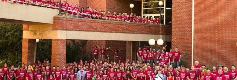 Hundreds of people wearing crimson t-shirts pose for a group photo on and below a skyway.