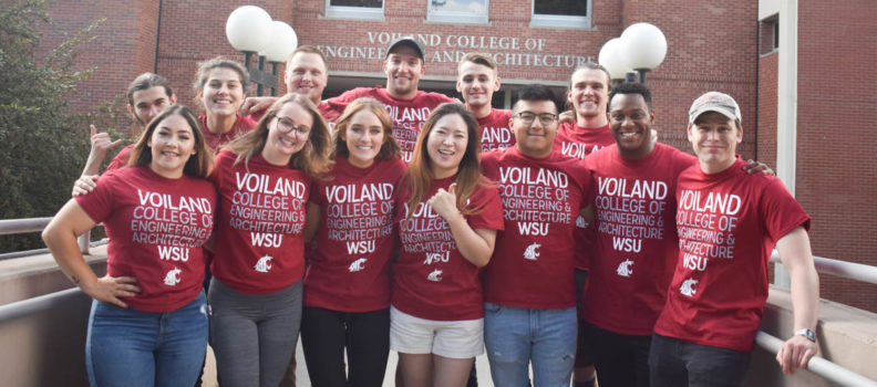 Voiland College tutors wearing crimson t-shirts pose in two rows for a group picture.