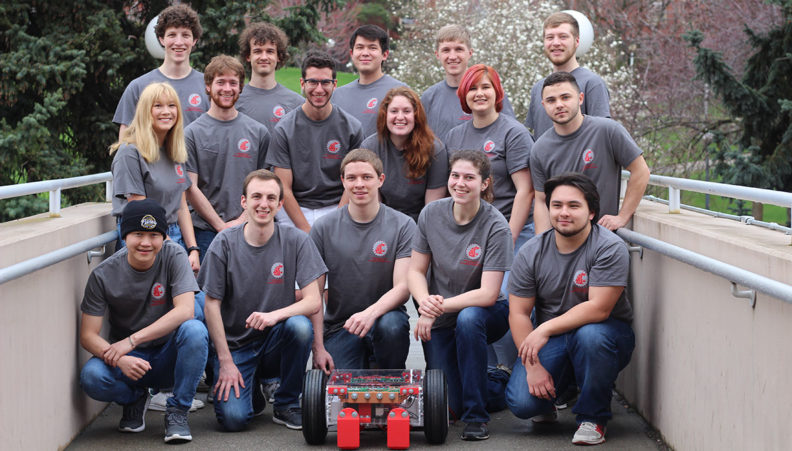 Sixteen robotics club members pose with a robot in front of Dana Hall in Pullman, WA.