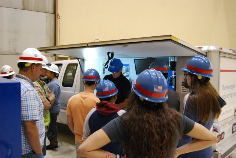Students listening to an employer presentation wearing hard hats