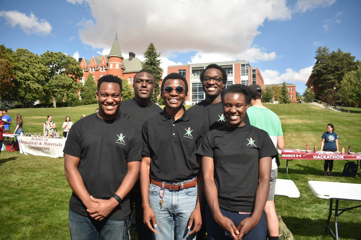 Four black engineering students pose by their National Society for Black Engineers booth.