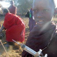 Maasai boy holds a syringe.