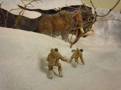 Miniature models of prehistoric people and a wooly mammoth in a diorama..