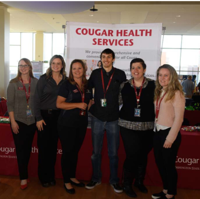 People standing in front of a Cougar Health Services booth.