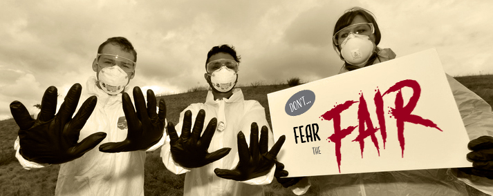 People in hazmat suits holding a 'Don't fear the fair' sign.