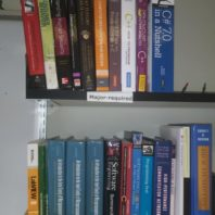 Computer science and engineering-related textbooks on a shelf.