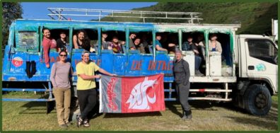 "Several WSU students hold the Cougar flag beside a customized passenger ""bus."""