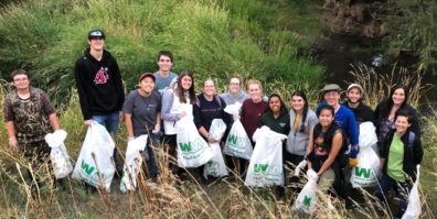 Group of students with trash bags at river