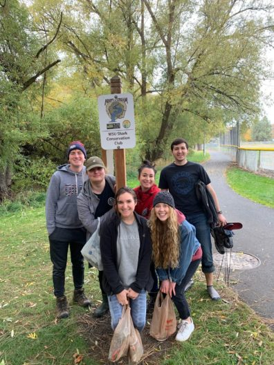 Group of students in front of sign that reads adopt a stream