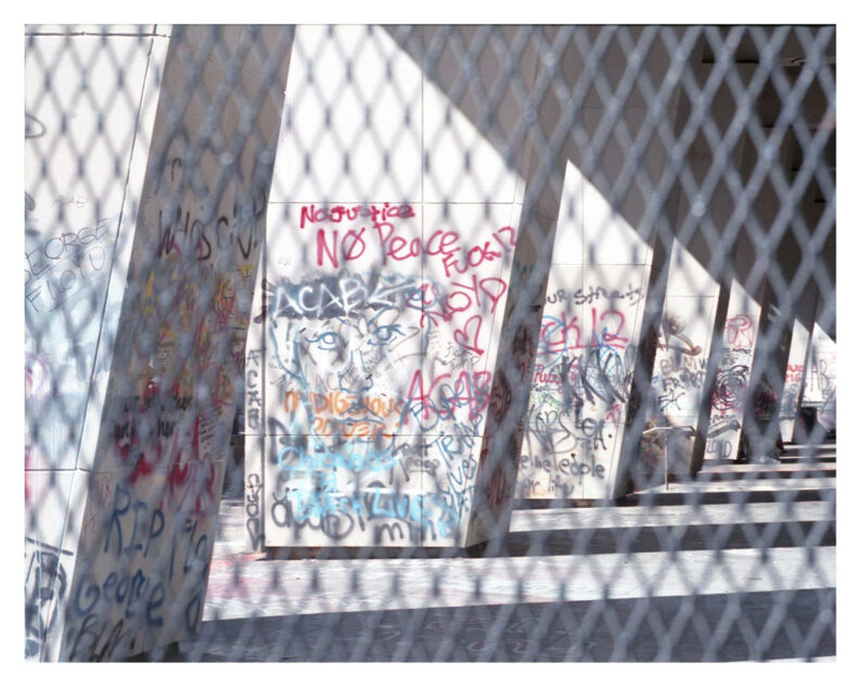 Photograph of graffiti through chain link fence