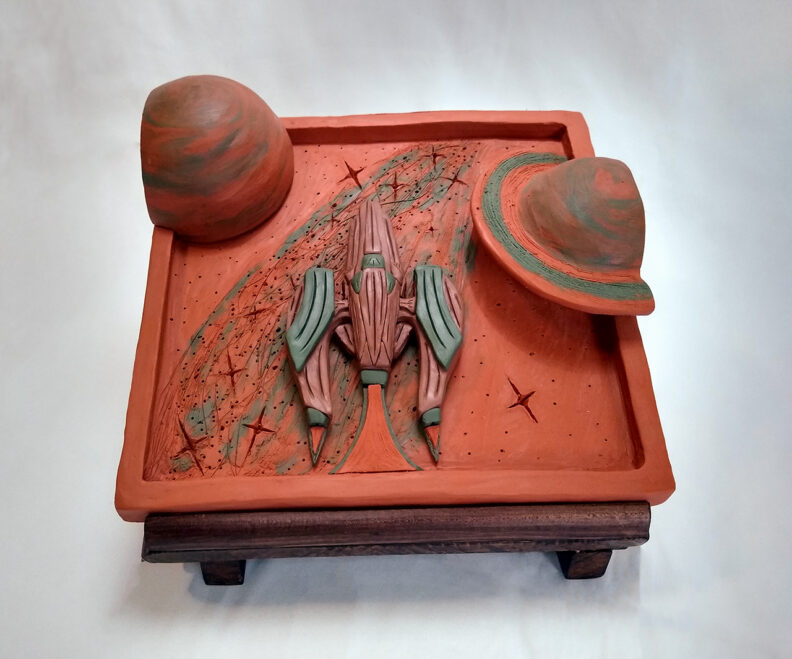 Clay sculpture of rocket ship and planets