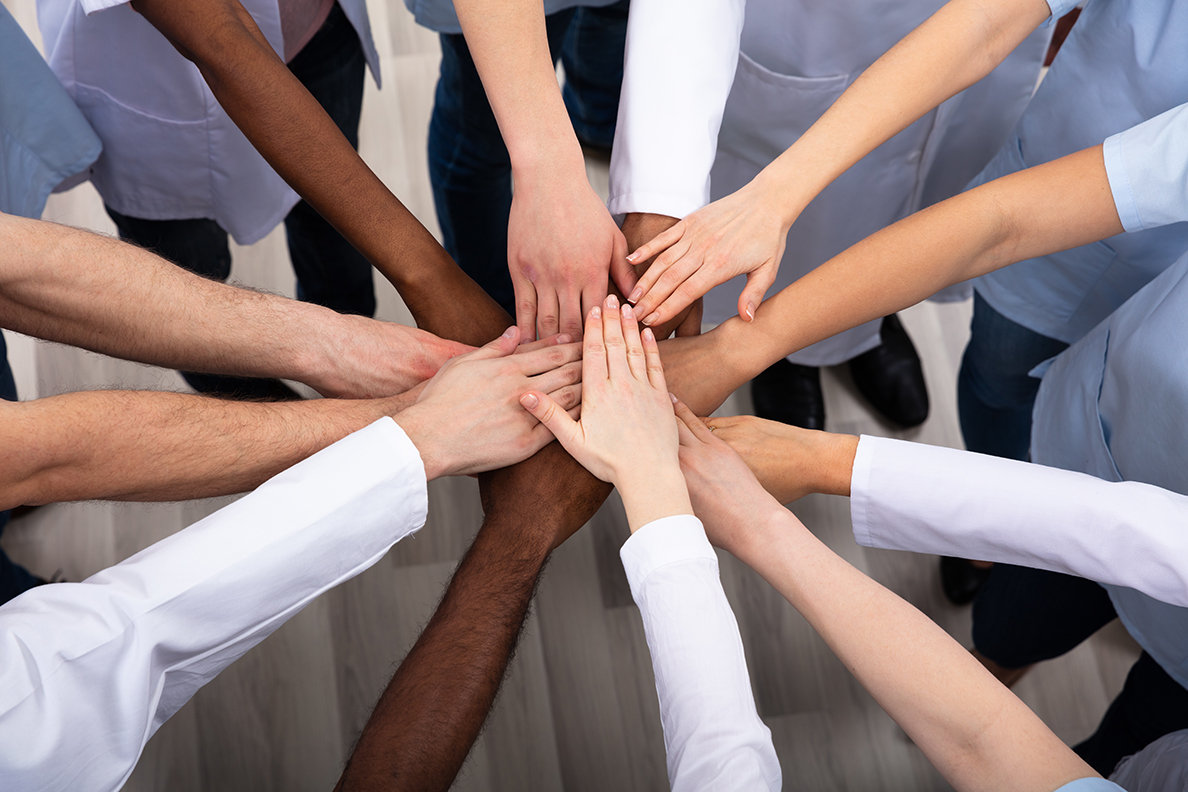 Group of people stacking hands in a circle.