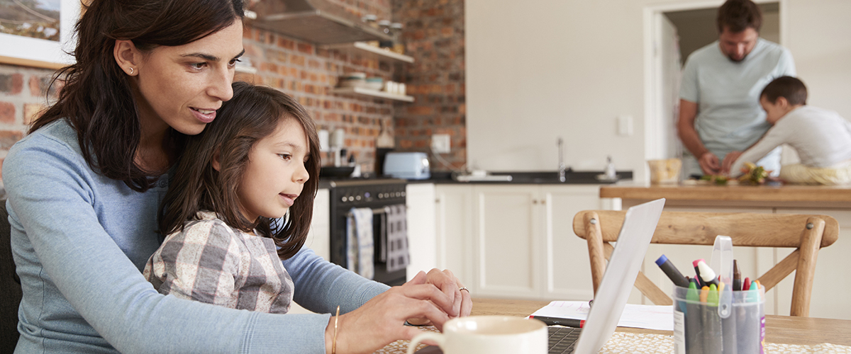 Photo: Busy Family Home With Mother Studying As Father Prepares Meal.