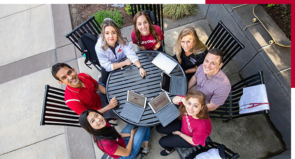 PHoto: Smiling group of students seated around outdoor table look up at overhead camera.