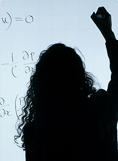 Silhouette of a woman writing equations on a board.