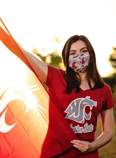 Female student holding wearing a face mask and holding a WSU Cougars flag.