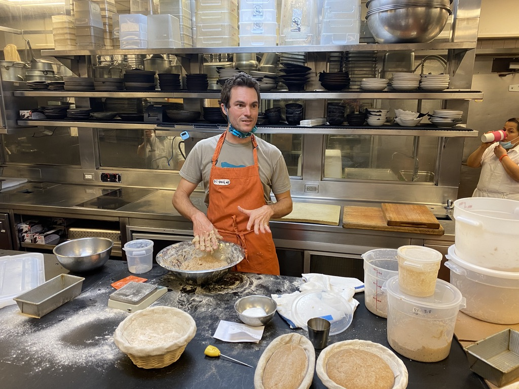 PhD student Louie Prager mixes dough in a commercial kitchen.