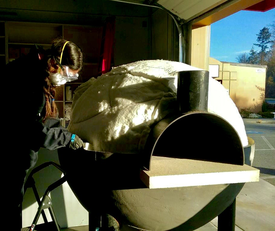 Special Projects lead Janine Johnson insulates a WW II submarine net buoy oven.