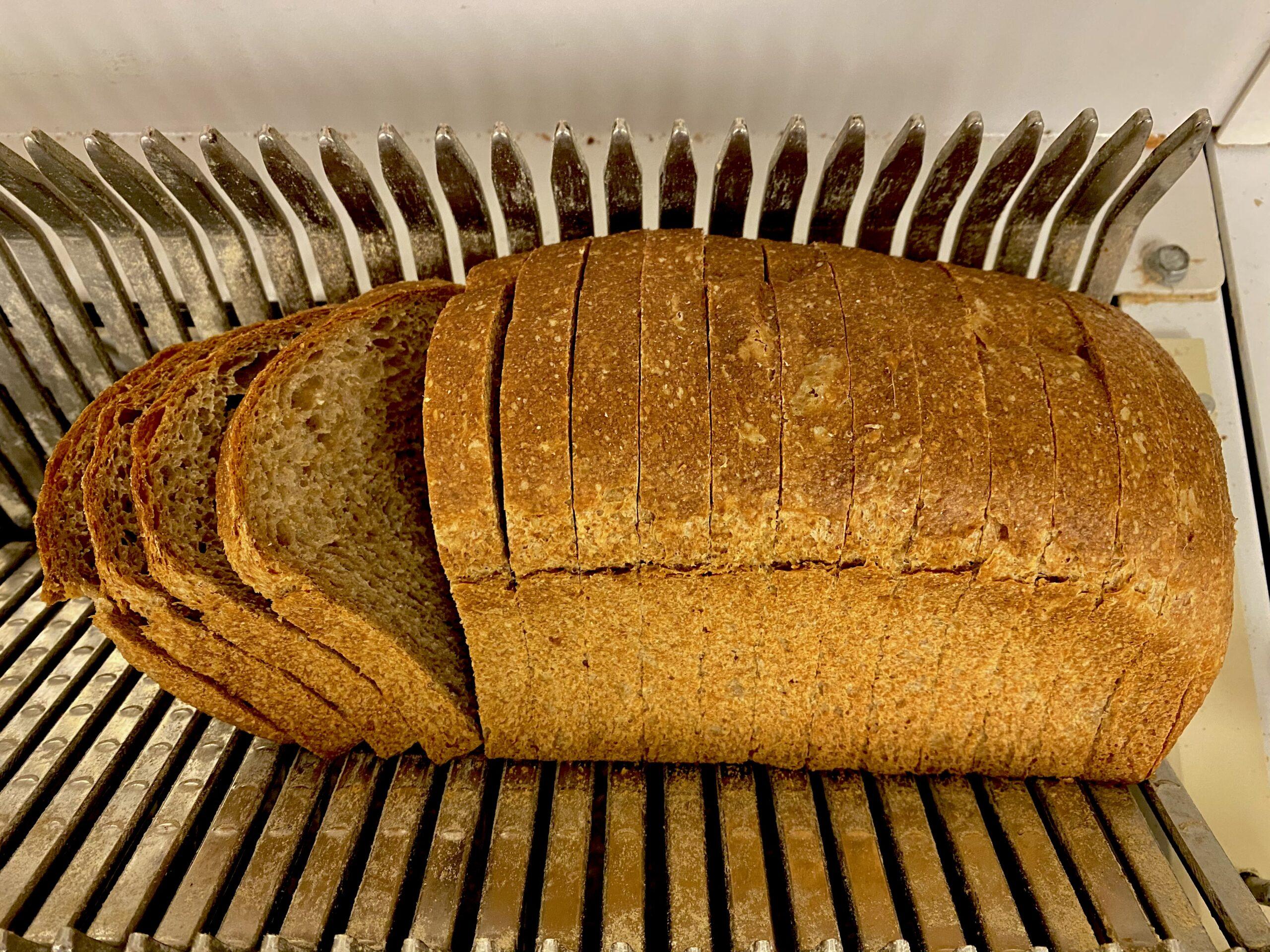 Sliced loaf of bread on a slicer.