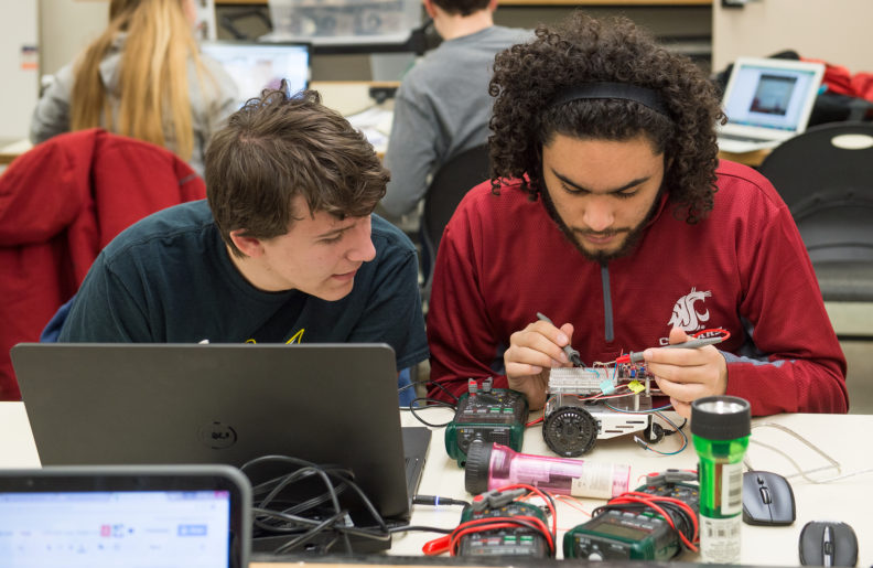 A student watches another student weld. The table they are sitting behind holds a laptop and several electronic controllers.