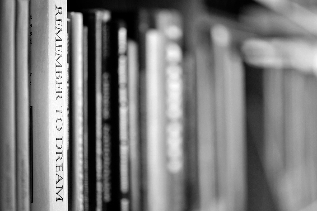 """Dramatic photo of books in monotone with one book exposed and in focus saying, """"Remember to dream"""""""