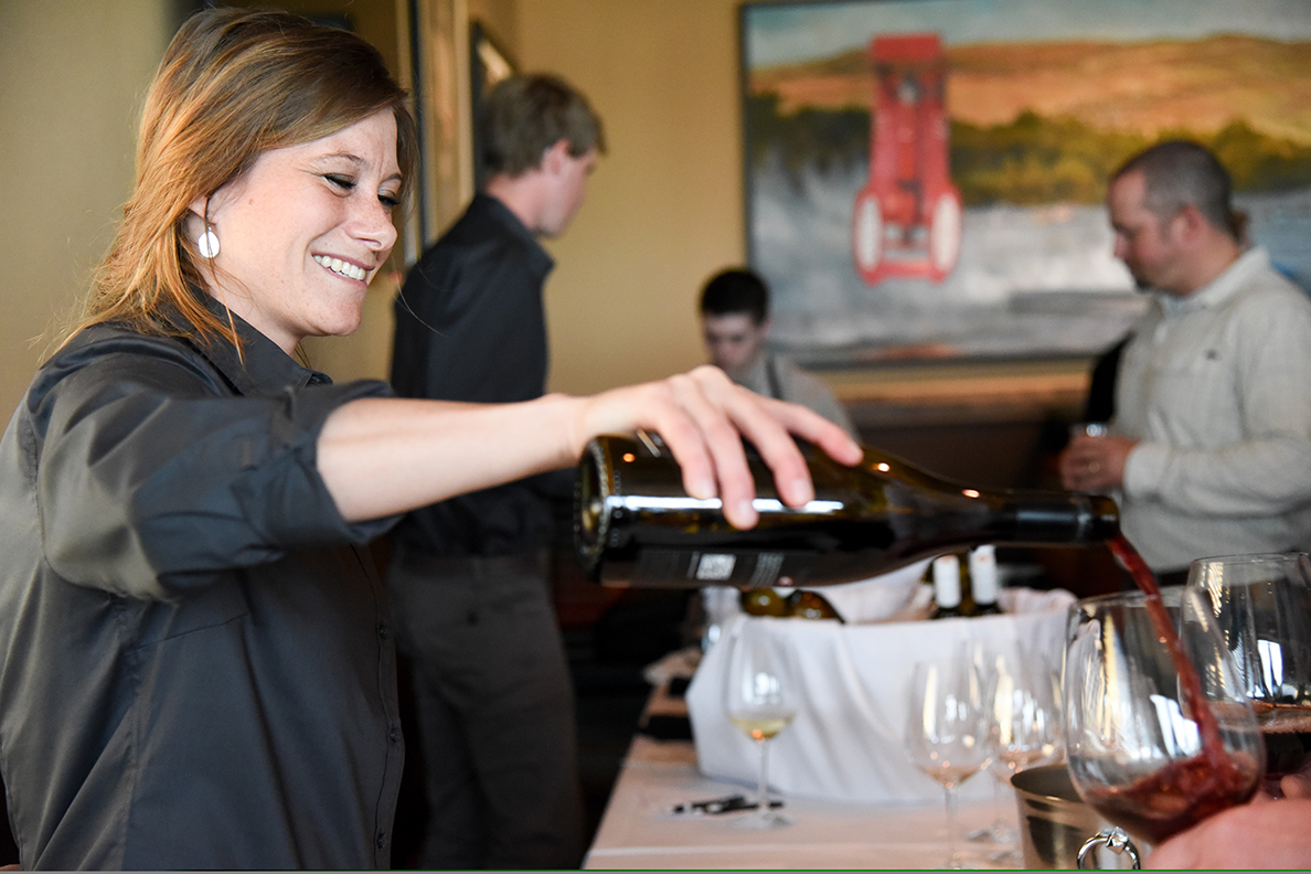 WSU Viticulture & Enology student pours blended wine at 2017 spring dinner.